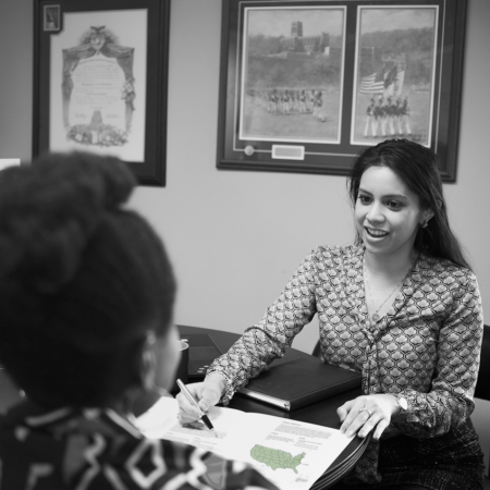 Image of an interview with TIME's HR Manager. A young woman sits at a desk explaining a graphic to another woman.
